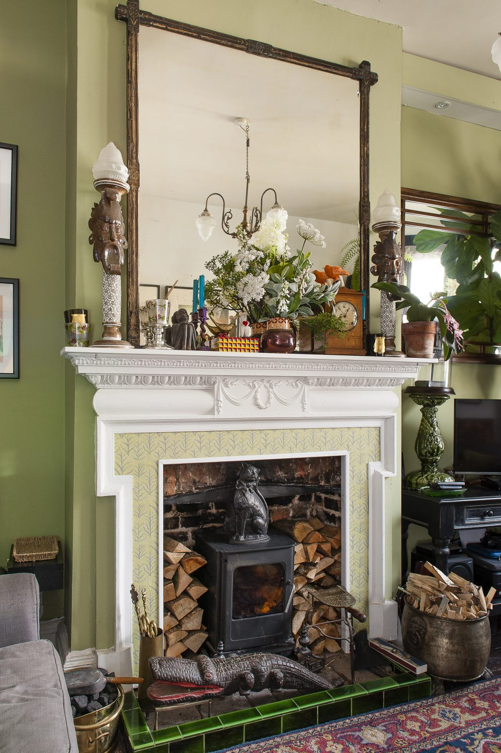 The impressive fireplace in the sitting room was an Ebay find, the surround wallpapered instead of tiled using paper from Vintage Bird