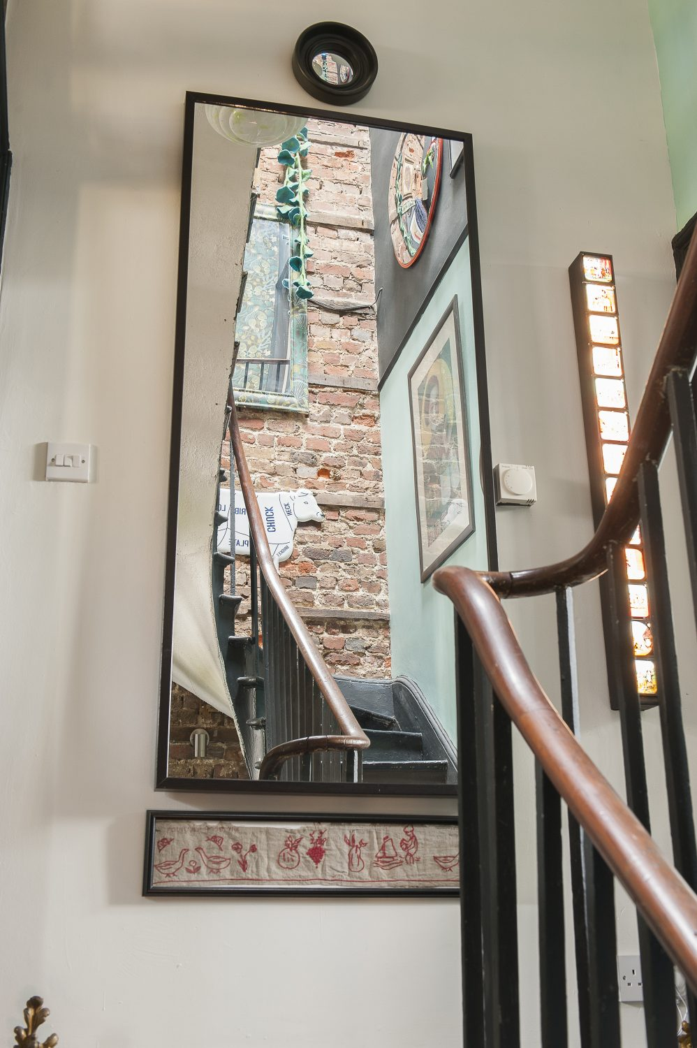 Strategically placed mirrors illuminate the potentially light-starved staircase that leads down to the stockroom in the basement