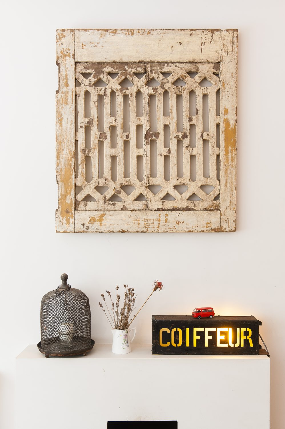 An old French chateau shutter on the living room wall is displayed like a piece of art above an illuminated coiffeur unit from a French hairdresser's, picked up in Lille at the Braderie France, a massive flea market