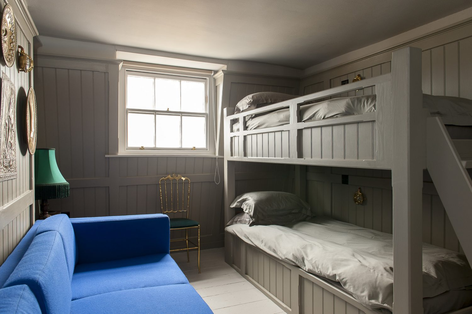The Crow's Nest's bunk bed den features a wall of pressed brass plates