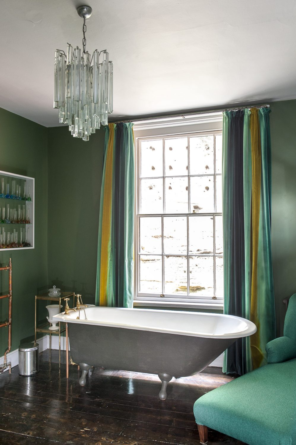 A roll top bath nestles within the bay window in the Captain's Room, with beautiful views out to sea