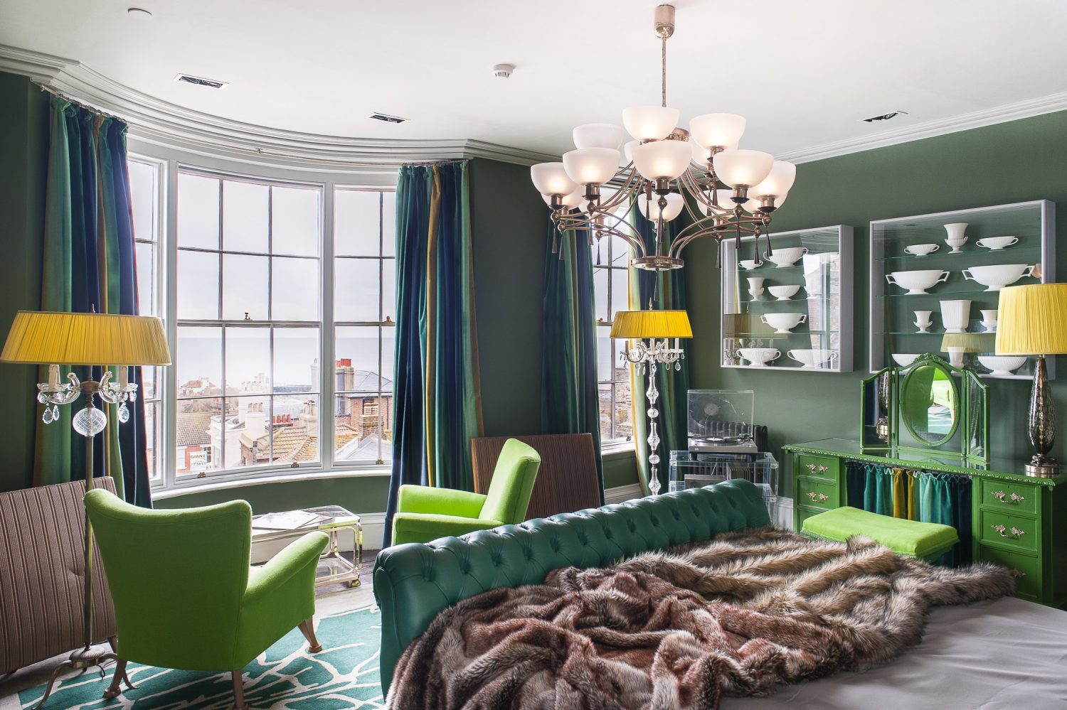 The stunning Admiral Suite is an eye-popping tableau of green fabulousness, encompassing the bespoke emerald green leather chesterfield bed frame, two Kelly green armchairs, the walls and a Louis Fooey dressing table and bedside tables painted in demi-gloss Kelly.