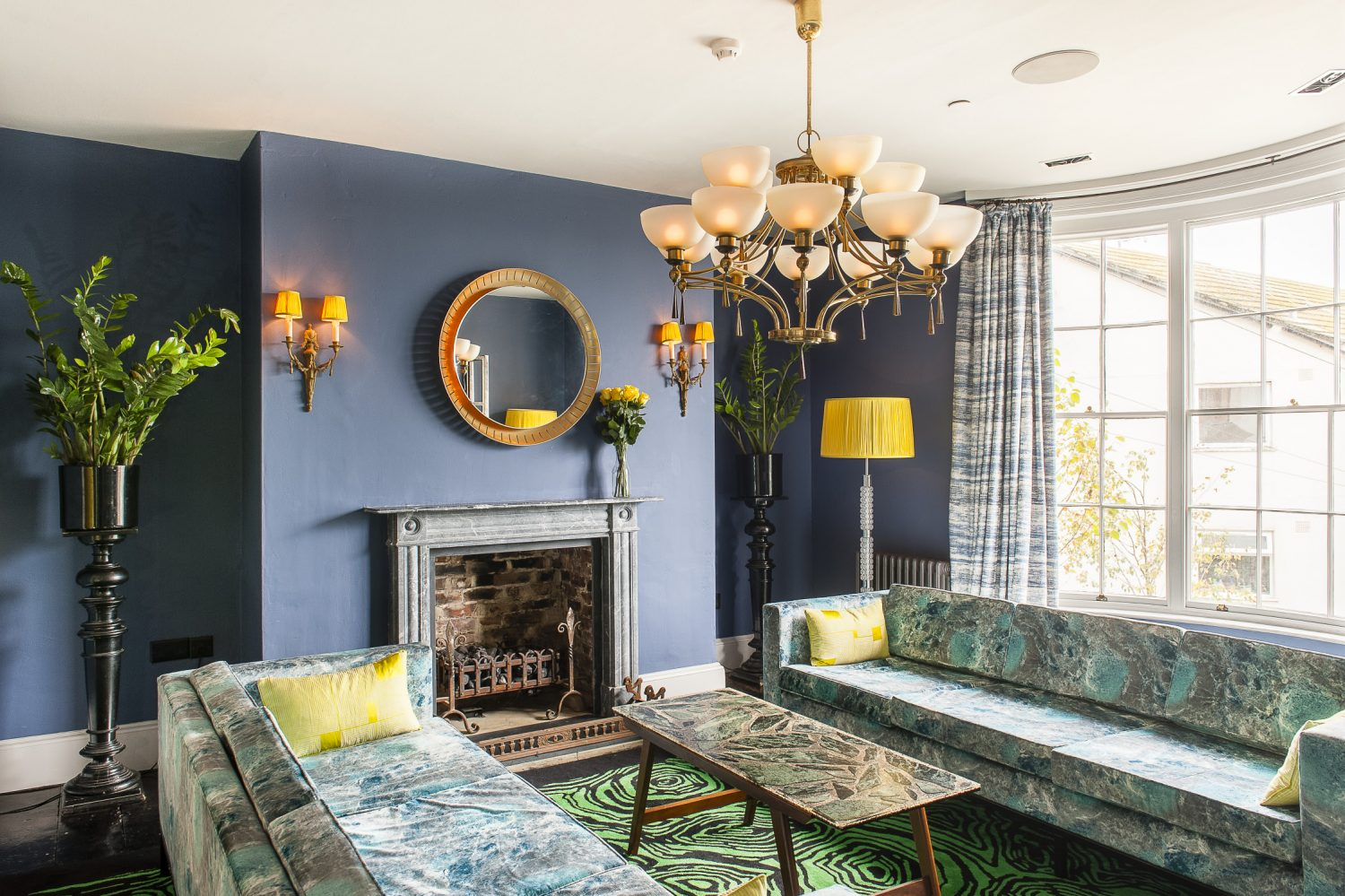 Two custom made marble-print velvet sofas sit below a 1940s brass chandelier in the sitting room