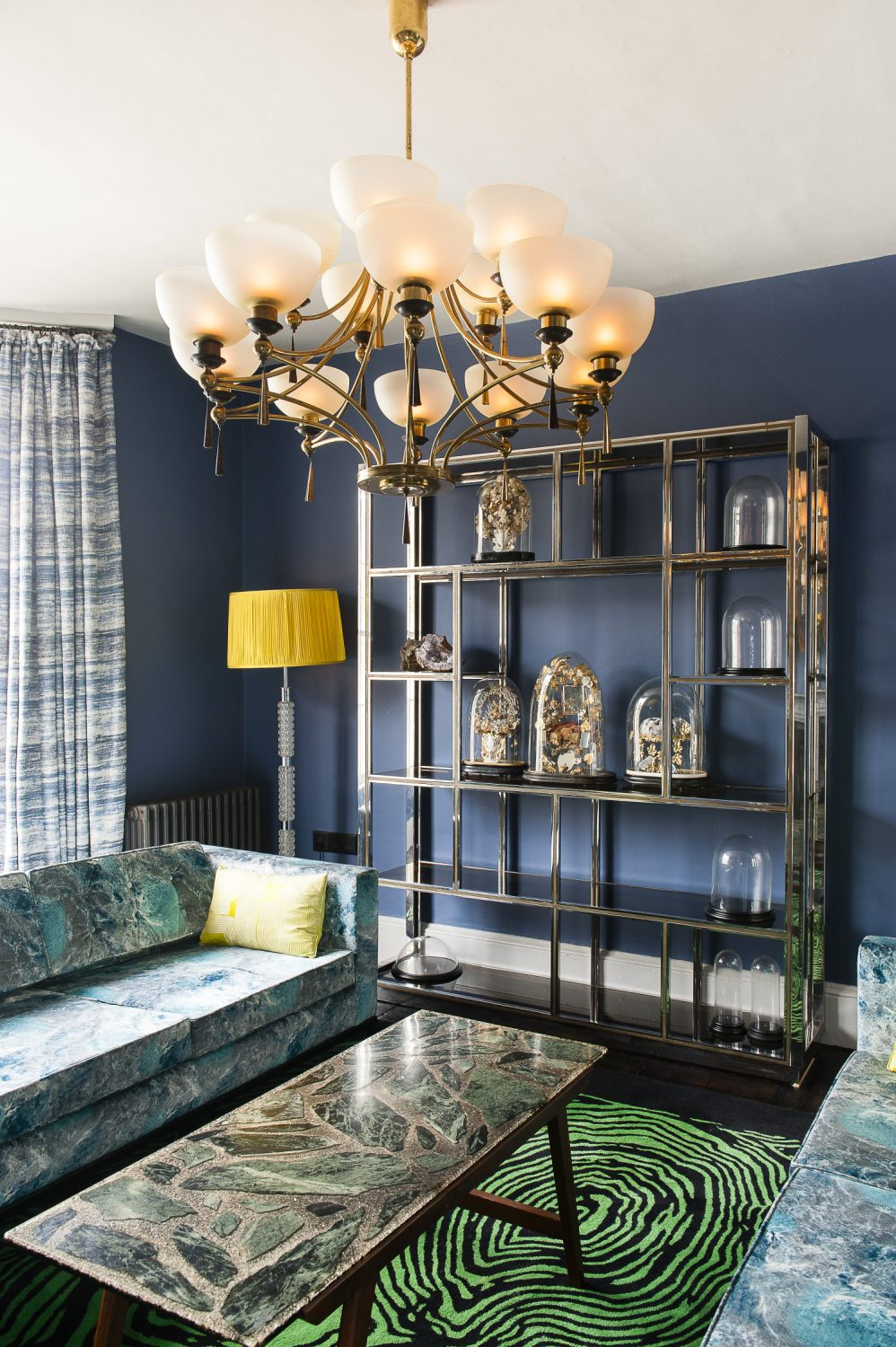 A 20th century vintage chrome shelving unit houses a collection of vintage French dômes du mariage