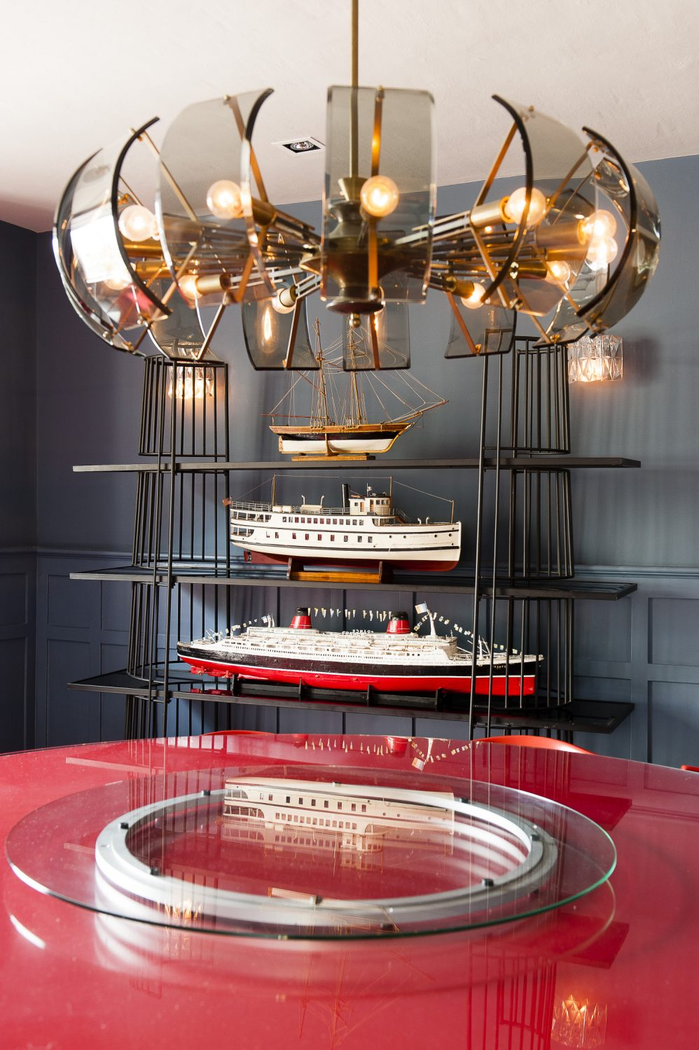 The dining room can seat ten around a huge round red table. 1950s metal and wood bookshelves display three large model boats from Ardingly, while opposite, glass-fronted original cupboards on either side of the fireplace display musters of stoneware, cabbage ware, pewter, silver and crystal