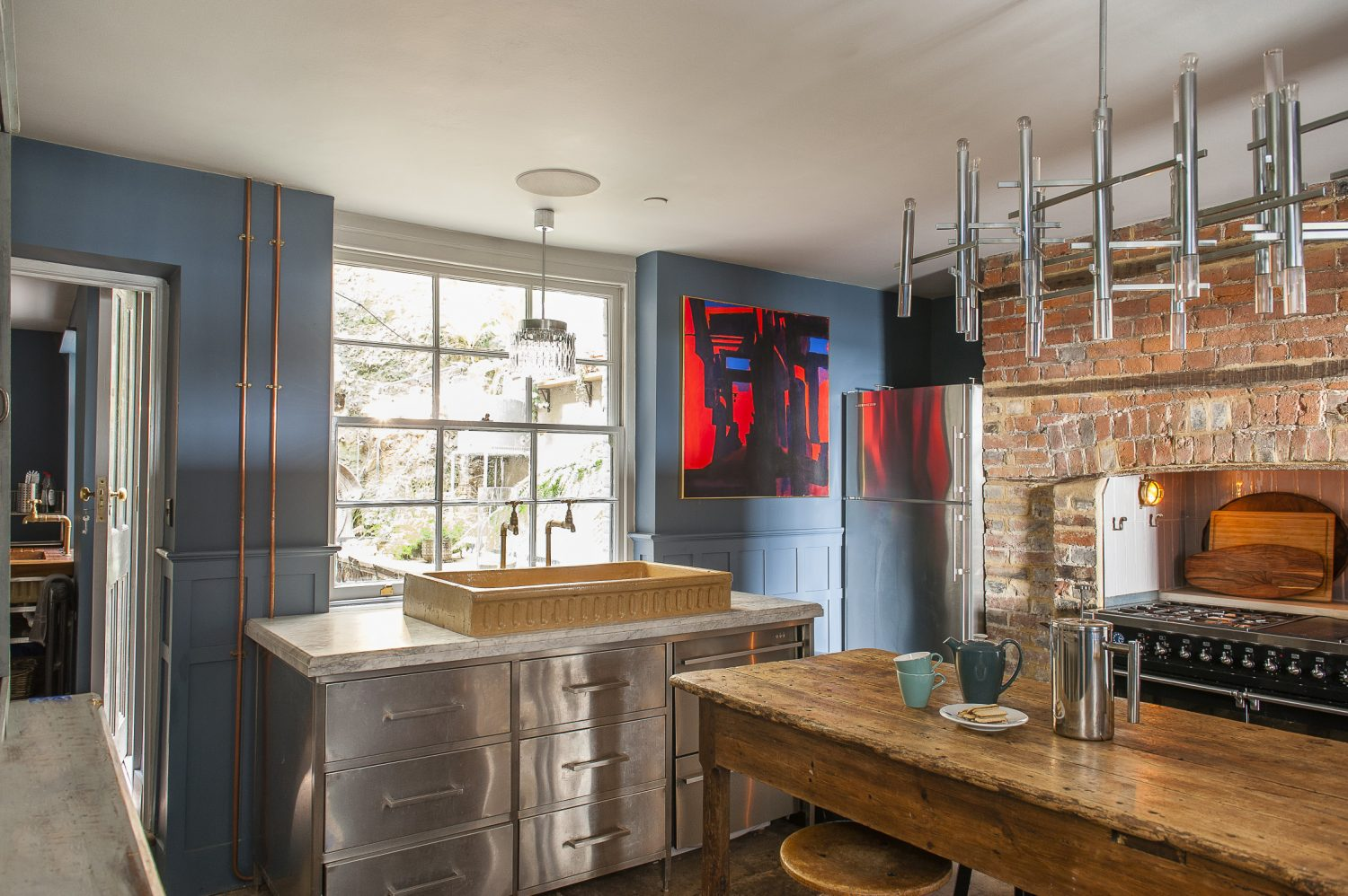 At the heart of the kitchen are a marble-topped stainless steel unit that Shaun had made to house the old stone sink and an 18th century oak refectory table