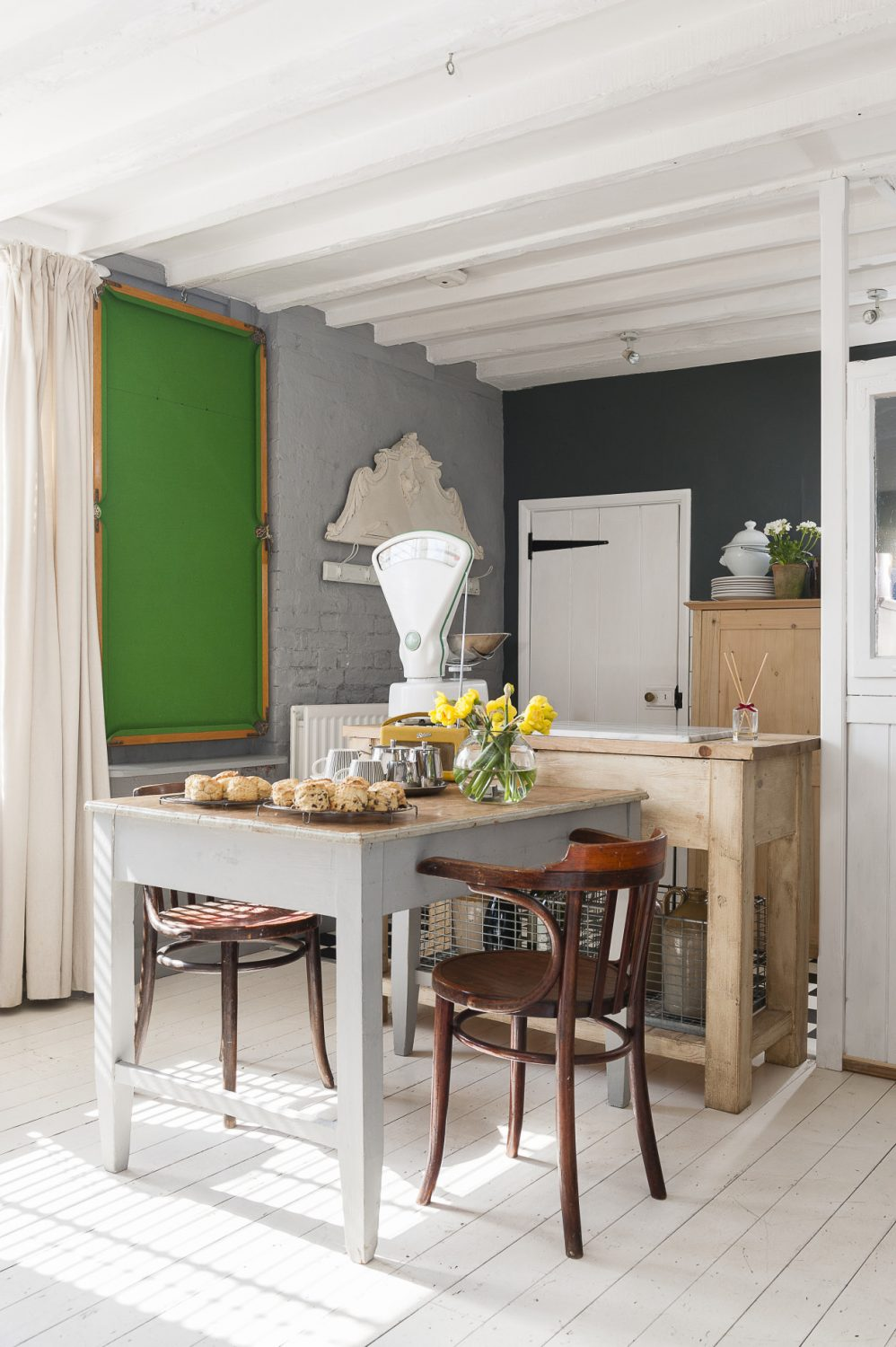 A snooker table hangs decoratively on the wall in the kitchen, bringing a splash of colour to the room, but it's also just waiting to be taken down for a game – and, by fluke, it fits perfectly on top of the dining table