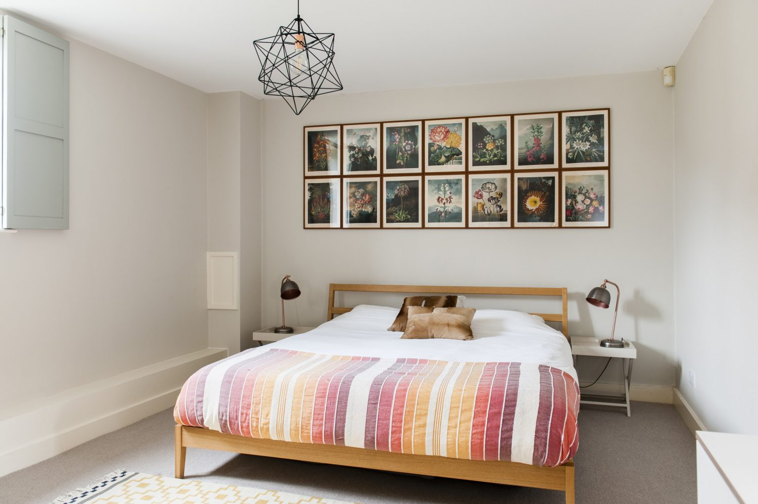 Another door from the dining area leads through to a generously sized bedroom, painted in Farrow & Ball Skimming Stone. A striking arrangement of framed flower prints hang over the headboard, taken from a book called the The Temple of Flora by a botanist Robert John Thornton