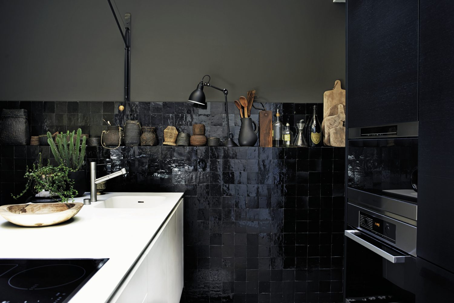 The black and white kitchen is lit by natural light from an atrium, so despite the glossy black tiles and bitter chocolate walls, the space is bright. A white island conceals storage and houses a sink and hob/stovetop. The part-tiled wall is built out enough to include a shallow shelf for utensils, chopping boards, bottles of olive oil, African baskets and a black Anglepoise lamp.