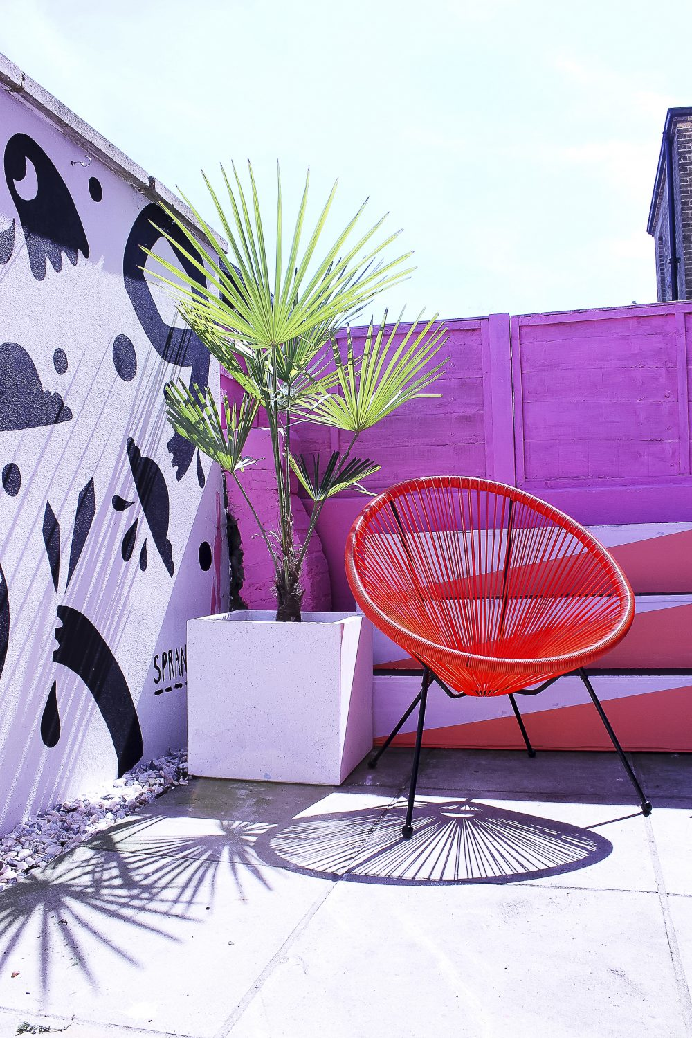 The kitchen looks out onto the courtyard garden. Amy shares a studio in Margate with her fashion designer housemate and another friend, the illustrator Sprankenstein, who designed the mural on the wall. Bubblegum pinks combined with red and potted palms give the garden an uplifting feel no matter the season