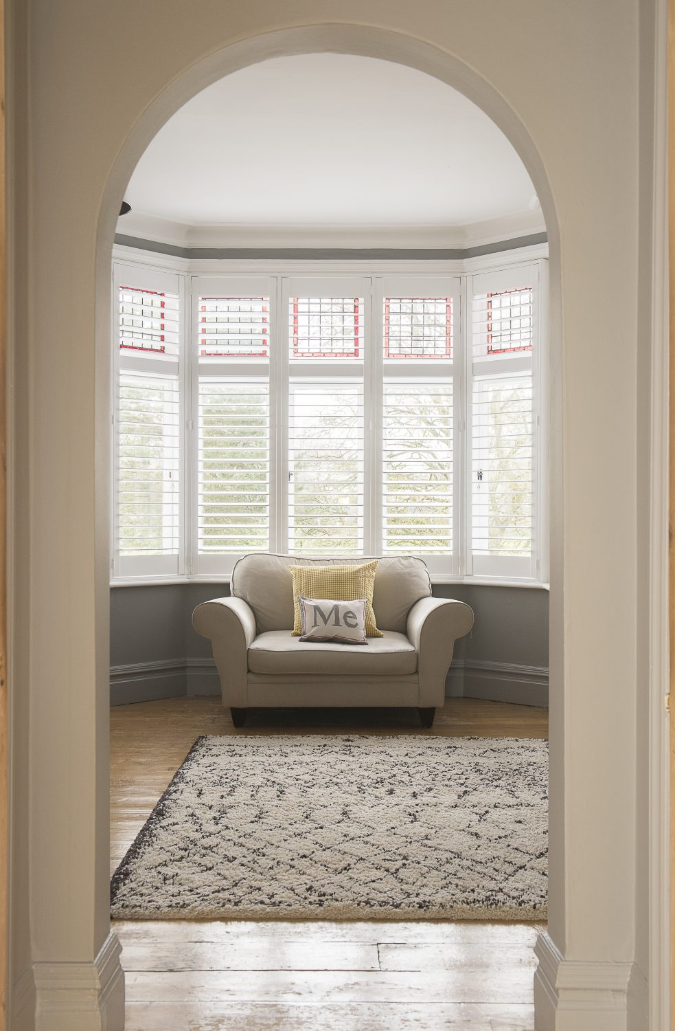 """In the master bedroom is a bay window and oversized armchair or 'love seat'. """"We've had the armchair for more than 10 years, along with the leather sofa downstairs. They were in the first flat we had together,"""" says Caroline"""