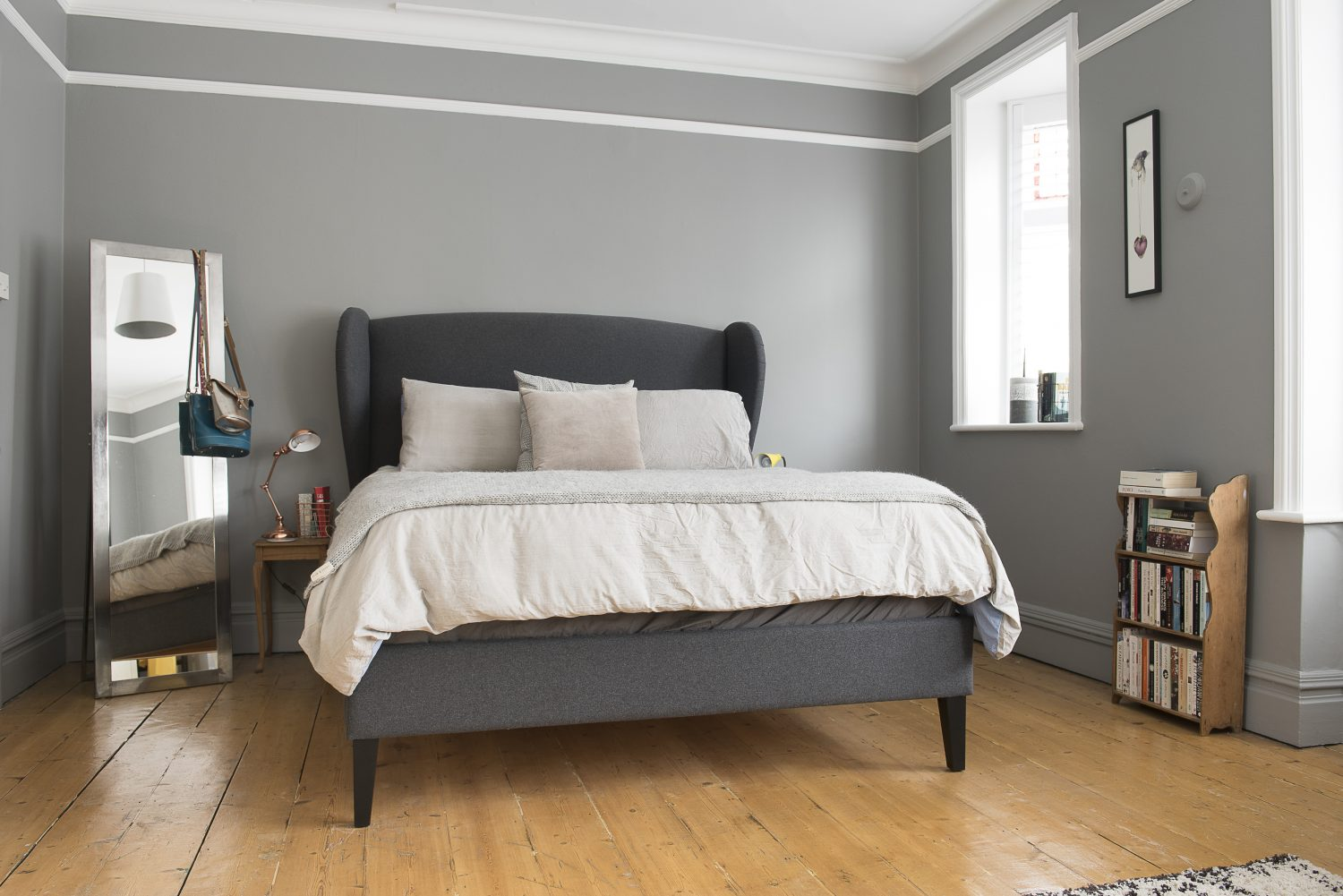 The walls of the master bedroom are painted in Manor House Gray by Farrow & Ball. A king-sized bed by Sofa.com takes pride of place next to a pretty lantern window