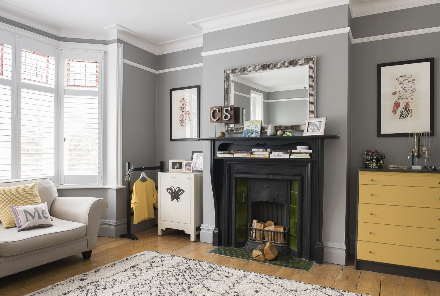 A brightly painted chest of drawers contrasts with the cool greys and blacks of the master bedroom