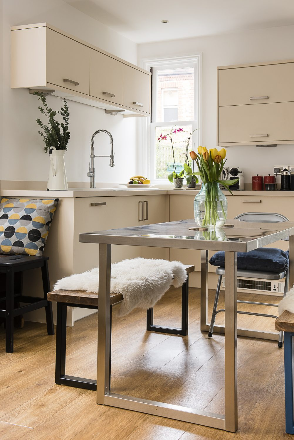 The kitchen's bi-fold doors open out into the courtyard garden. Caroline sourced the metal kitchen table from eBay
