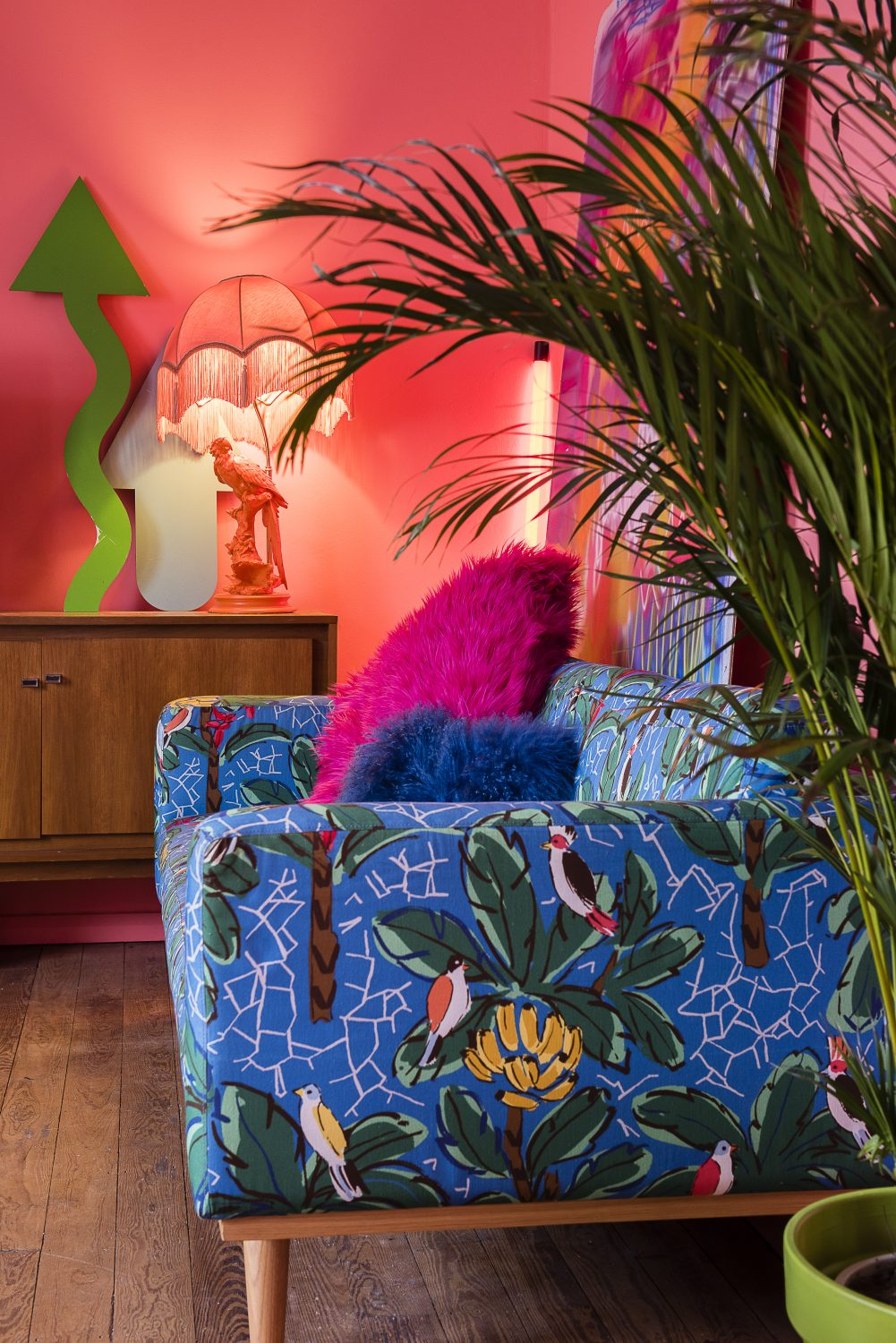 Tropical birds and foliage feature on the upholstery of another sofa, alongside a neon light and a large spray-painted canvas which rests against one wall