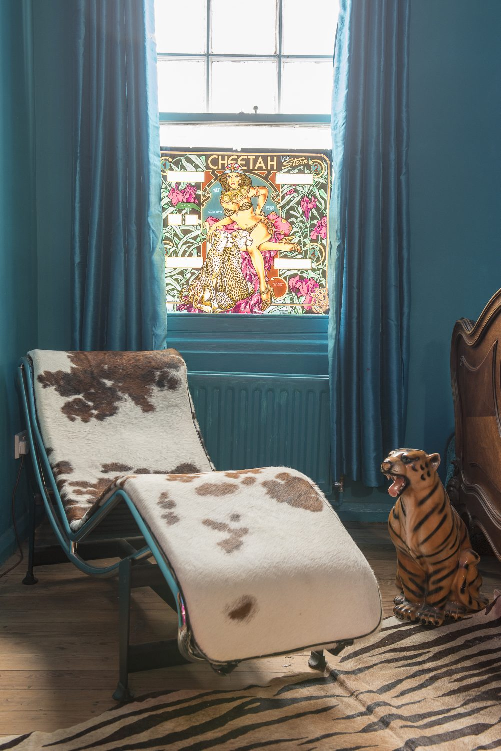 The bedroom's curtains perfectly match the teal used to paint the windows, radiator and walls