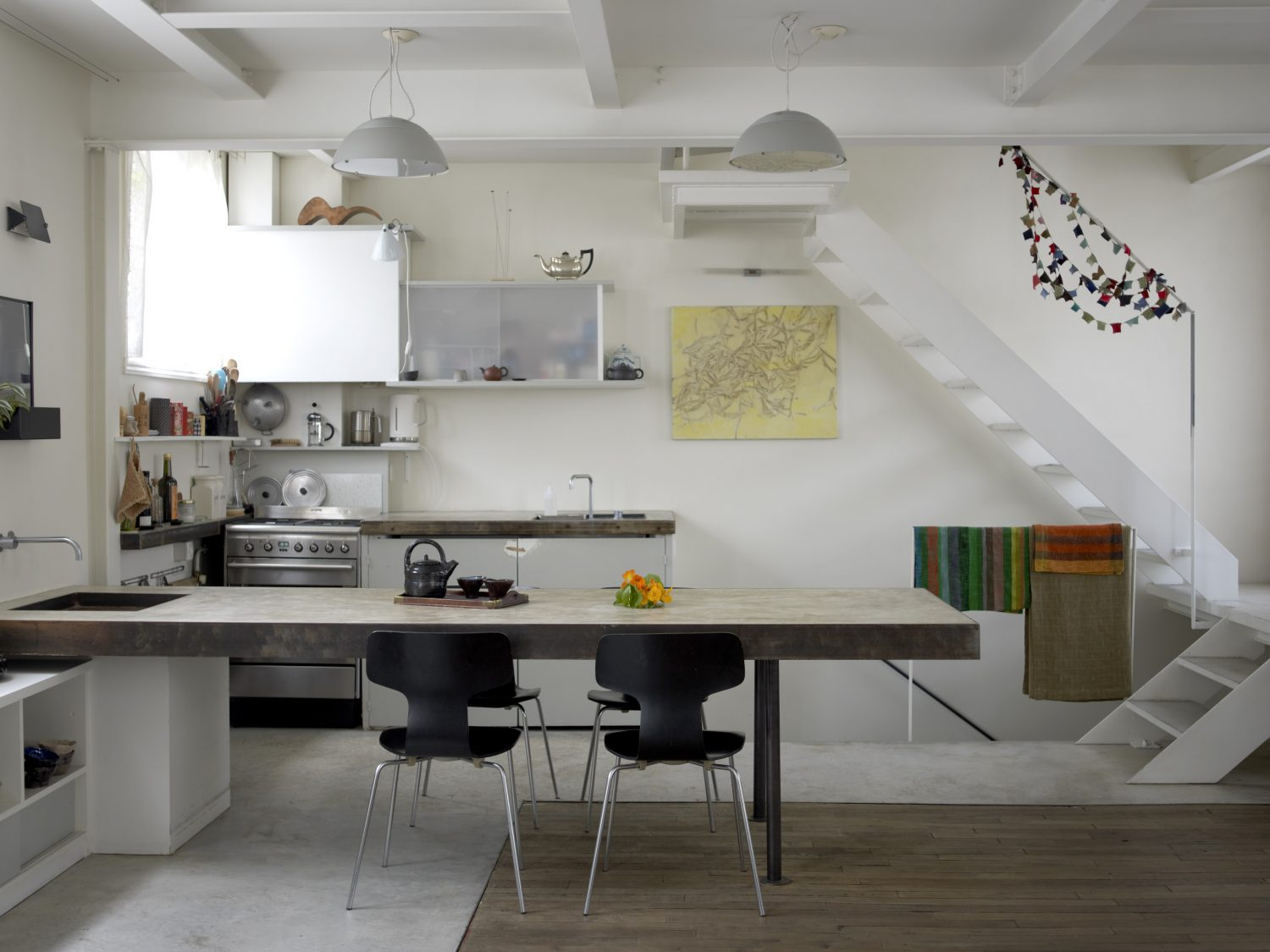 Smart Spaces: In the Parisian home of artist Cécile Daladier and architect/designer Nicolas Soulier (above), the kitchen sink is integrated into the dining table, doubling up as a cook's work surface when not an eating area. Quirky finds, like a silver Aladdin's teapot on top of the cabinets and the handmade bowls, create areas of visual interest. Overall, they've kept the colour scheme white, giving this bijou space a sense of airiness.