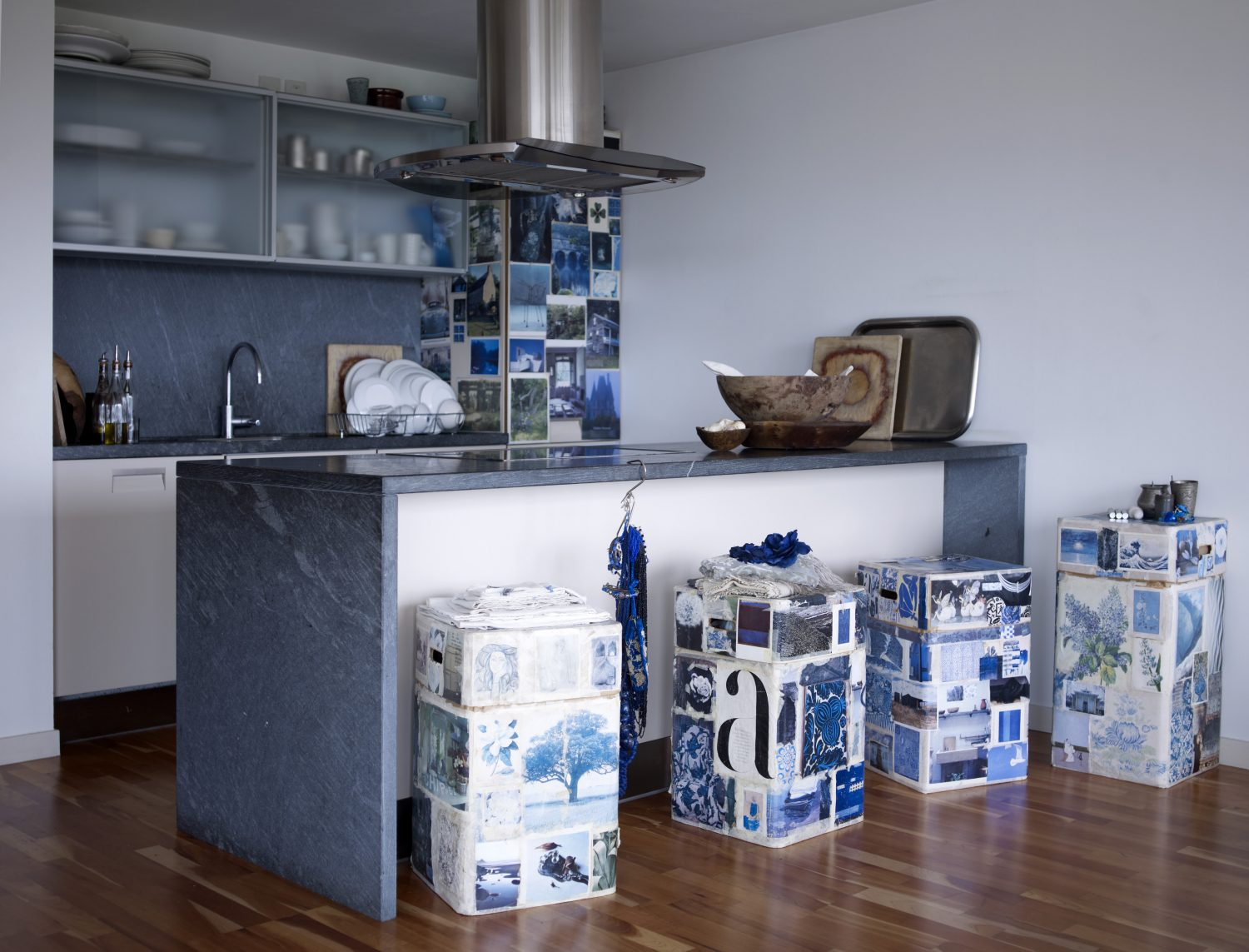 Blue & White: London based creative Ann Shore has put together a striking kitchen with her fresh, arresting palette of white and blue. She has used small pieces of masking tape to cover the fridge in a montage of blue and white images, including old magazine spreads, postcards and printed photos from around the world. Carrying on this theme, Ann has papered her breakfast bar stools – made from tall cardboard storage boxes – in recommissioned pages from books and magazines, to create a patchwork of memory and nostaglia. Her granite worktop on the cooking island carries on the theme, juxtaposed with crisp white cupboards. Wooden bowls and chopping boards bring in a sense of nature, like pieces of driftwood on a seashore, and contrast with the modern, polished-aluminium extractor hood.