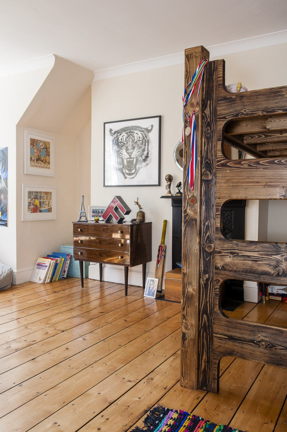 Their son's room has an elevated bed made from stained timbers. The 1950s chest of drawers was found in a charity shop in London and the F - the first letter of their son's name - was an online find.