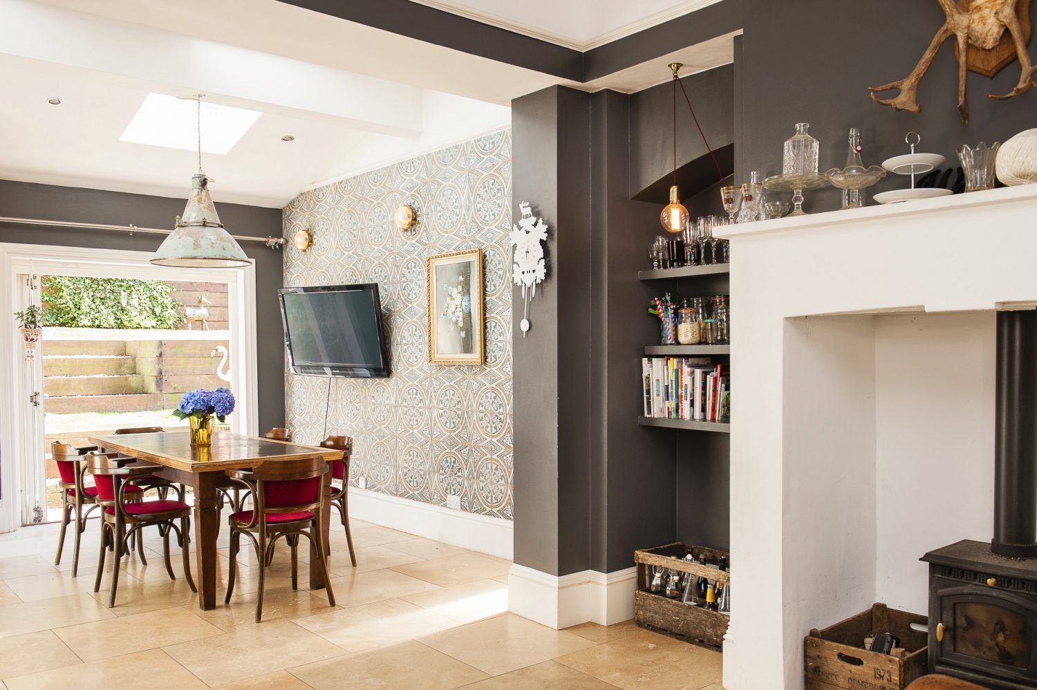 The walls of the kitchen are painted in Charcoal by Valspar. The tiles for the feature wall are from Topps Tiles. They bought the leather club chair in London years ago