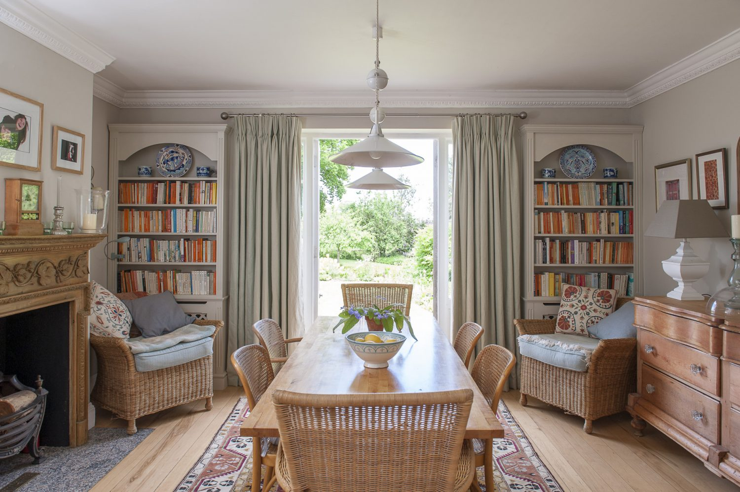 The breakfast room walls are painted in Farrow & Ball Shaded White, the plain wooden floors softened with rugs and kilims. The pretty pine fireplace was found in The Pantiles and the large Swedish chest opposite was one of the first pieces of furniture Tony and Debbie ever bought.