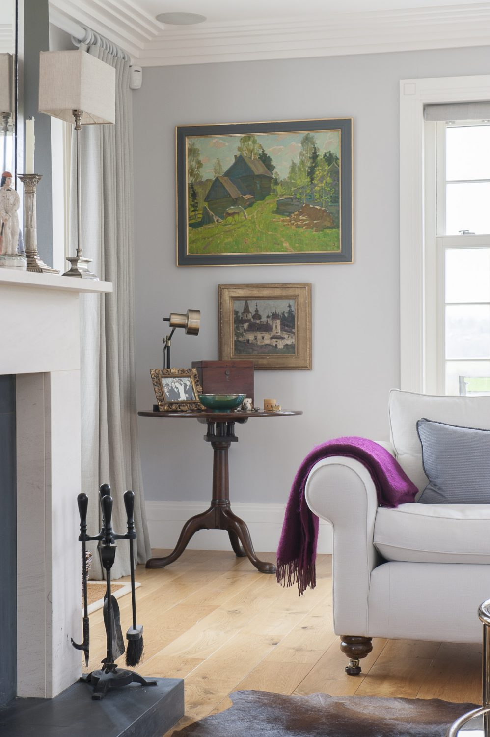 Bright oil paintings and a rich pink blanket add colour to the simple but comfortable living area