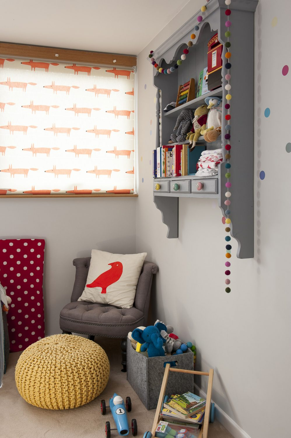 Newborn Max's room is yet to be occupied. The muted greys of the walls and furniture contrast with pops of vibrant orange from the roller blind in 'Mr Fox' fabric by Scion