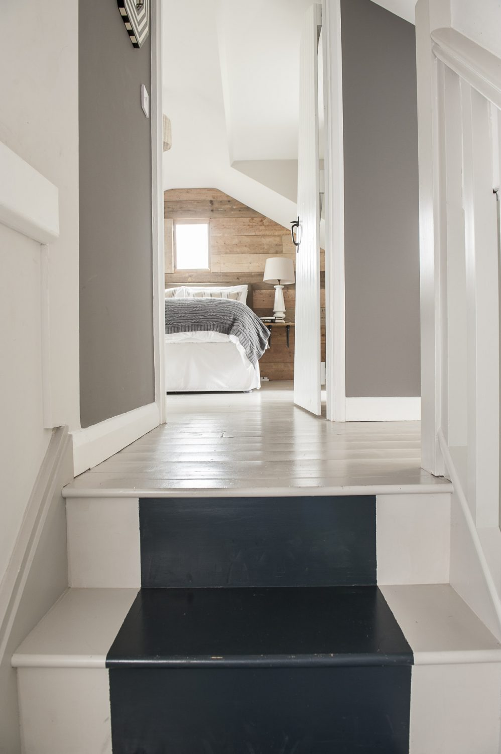 Stairs painted in Purbeck Stone with runner in Railings lead up to the vaulted master bedroom with a view to the sea