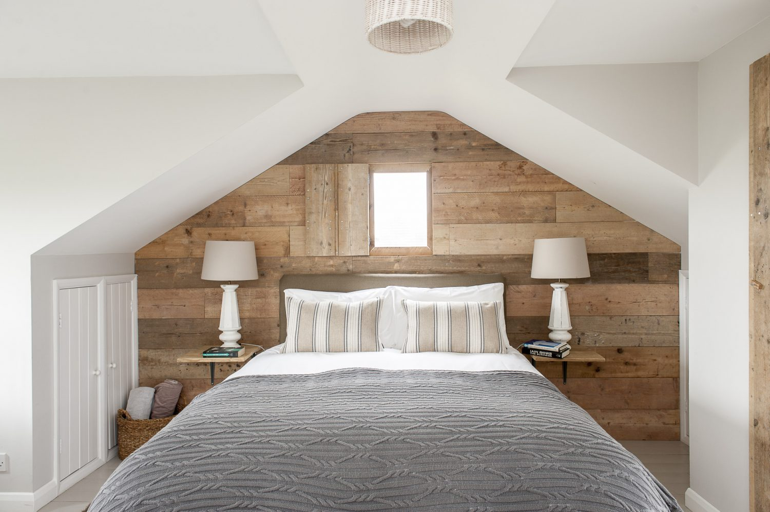 The wall of the master bedroom is clad in the same sanded scaffolding planks. The bedside lamps are from McCully & Crane. Francesca designed the headboard. The cushions are covered in Ralph Lauren fabric and the throw is from John Lewis