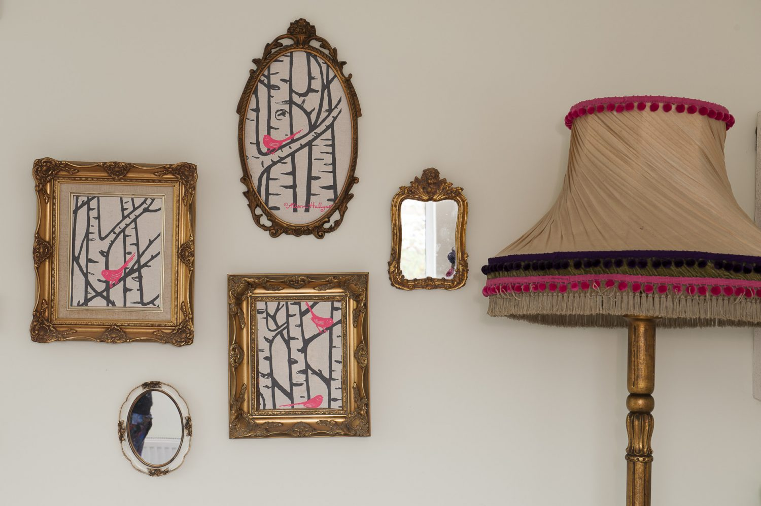 On the wall of the master bedroom Sandra has displayed three pieces of fabric by Alison Hullyer in gilt frames. She found the standard lamp at the Hospice in the Weald in Cranbrook, which she gilded before adding a bright pink and purple bobble trim to its shade
