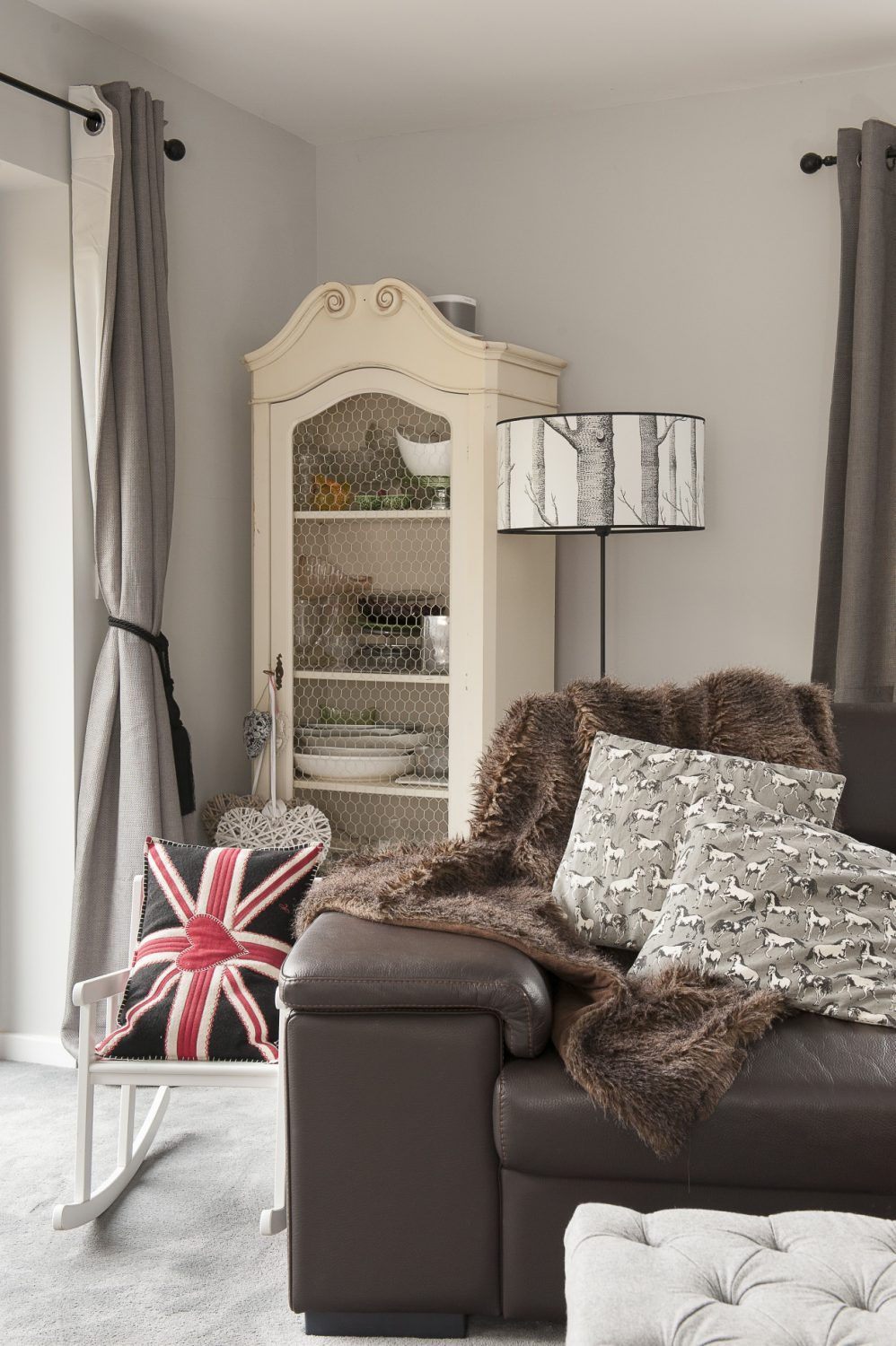 The sitting room is spacious enough to house a huge, leather L-shaped sofa. In one corner, next to a lamp with a shade that echoes the wallpaper opposite it, stands a distressed French armoire with chicken wire front