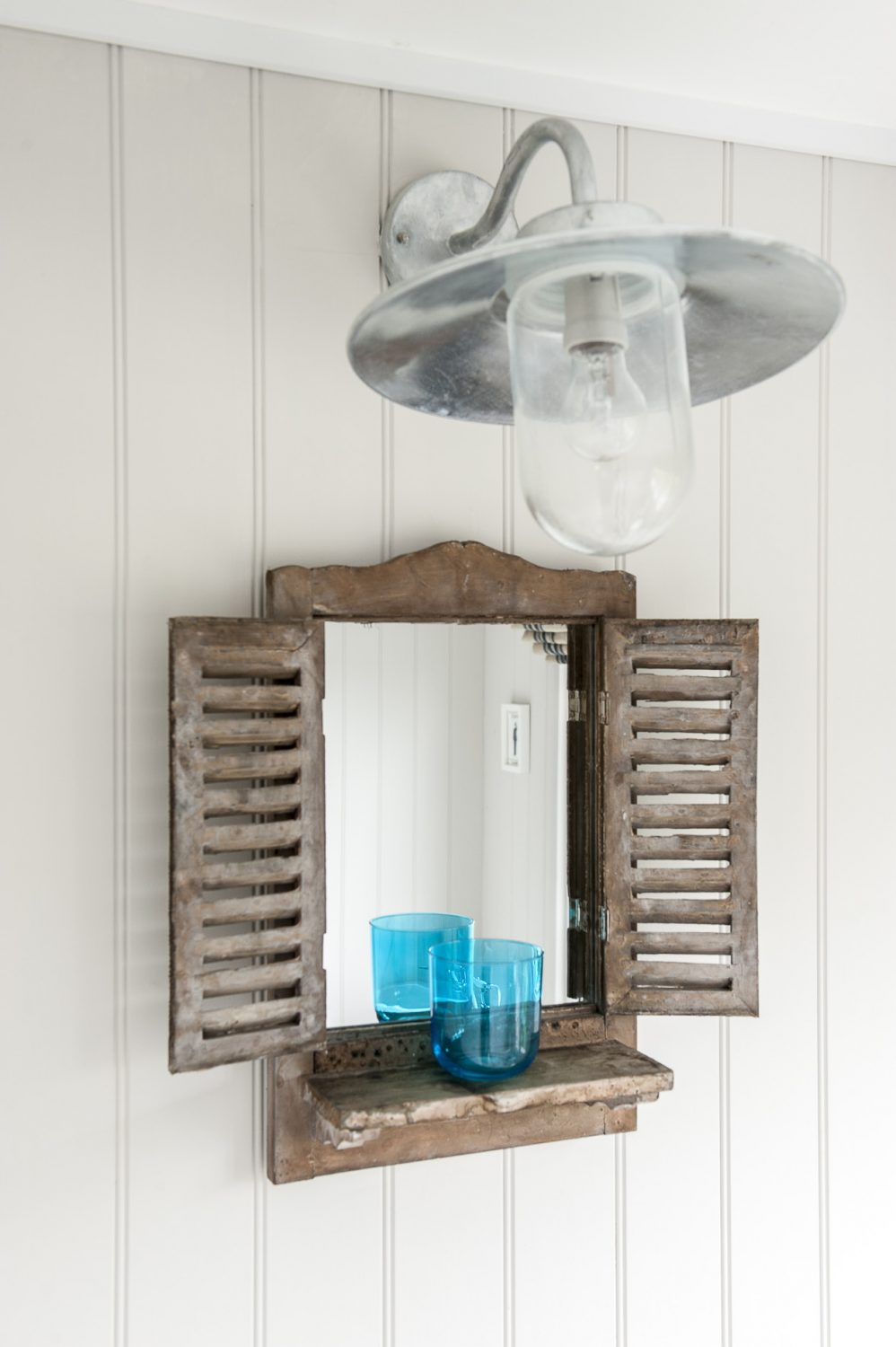 The shuttered mirror in the bathroom is from Strand Antiques and the industrial style light fitting is from Cox & Cox. The blue glass is from LSA International