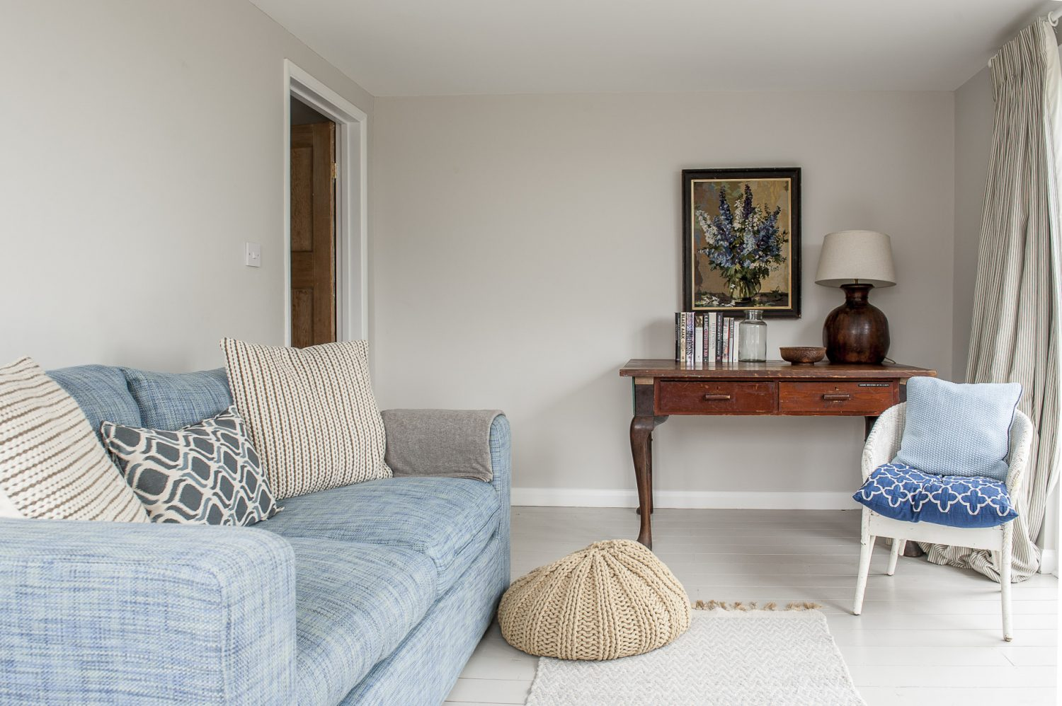 The sofa in the games room is from sofa.com while its cushions and those on the Lloyd Loom chair are covered in fabric by Merchant and Mills. The high desk, used as a side table, is from McCully & Crane