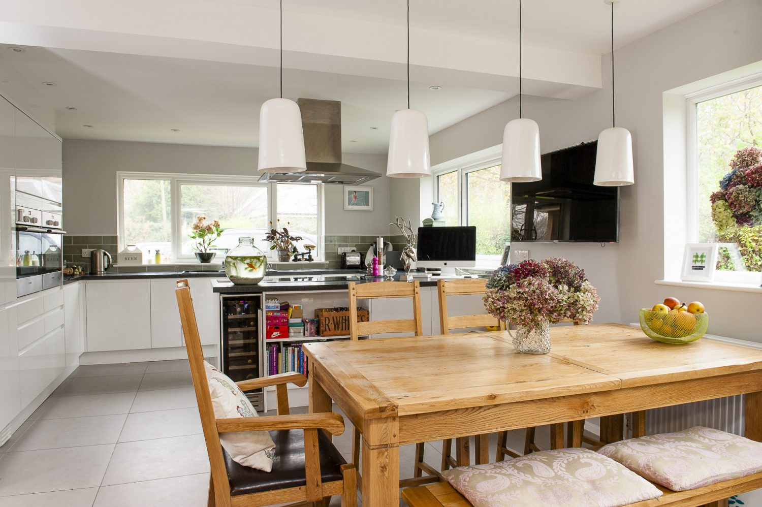 Over the dining table from the Simply Oak range from House of Oak are glass-shaded lights from John Lewis that look uniform but take on individual characteristics when lit