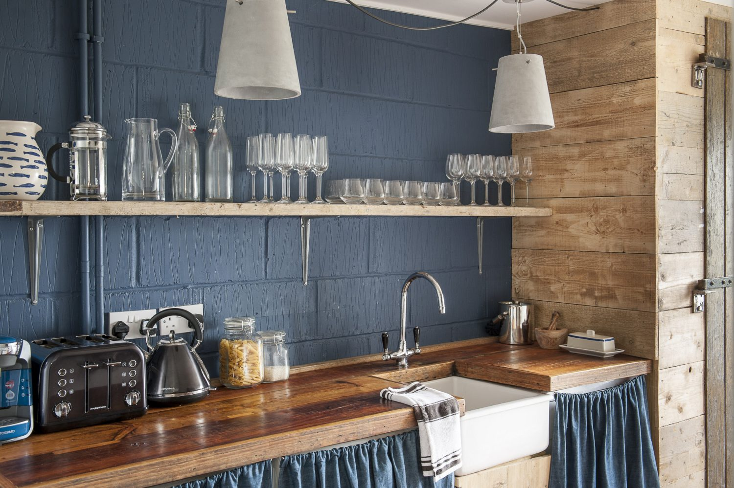 """Francesca """"doesn't do"""" fitted kitchens. The natural wood shelving and a work surface were made by H&B Wood Recycling. The full height cupboard was made by Francesca's father from old wooden tractor trailer doors. Blue curtains in denim by Merchant & Mills in Rye cover the dishwasher, freezer and washing machine. The kitchen walls are painted in Ammonite and Stiffkey Blue by Farrow & Ball"""