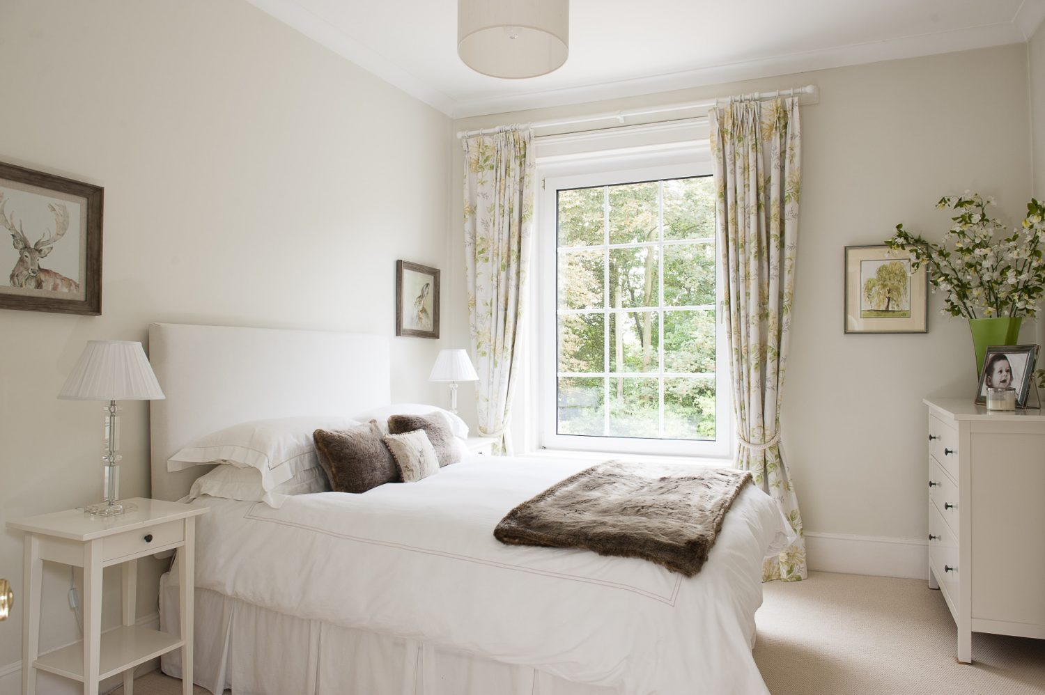 A guest room, painted in F&B's James White, features honeysuckle print curtains, limed wood furniture from The Vintage Home Co in Westerham and delicate drawings and paintings of landscapes and woodland animals