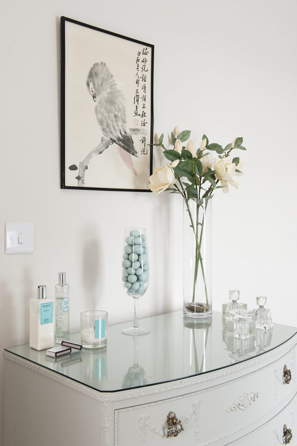 In the first guest room the walls are also painted with Skimming Stone, but here the colour looks more of a cool grey and the accents are in robin's egg blue. A chest of drawers displays a collection of Art Deco perfume bottles and a glass bonbon jar holds a clutch of speckled robin's eggs