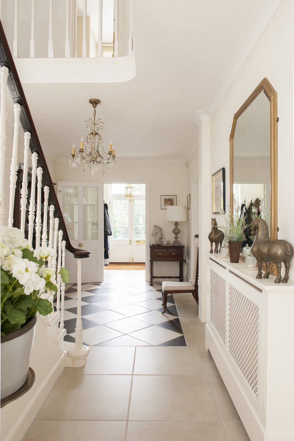 Visitors to the house step into the original, classic Regency hallway with a black and white diamond-tiled floor and a sinuous staircase that invitingly curves up and around to the upper storey