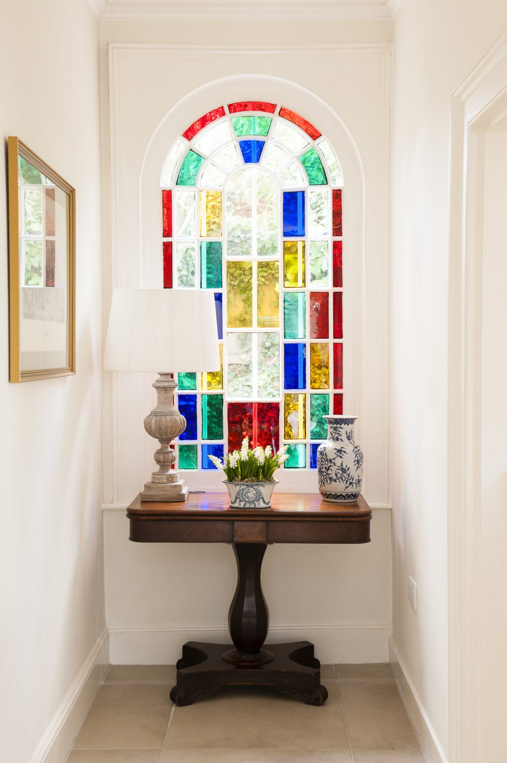 A stained glass window adds a pop of colour to the cool white hallway