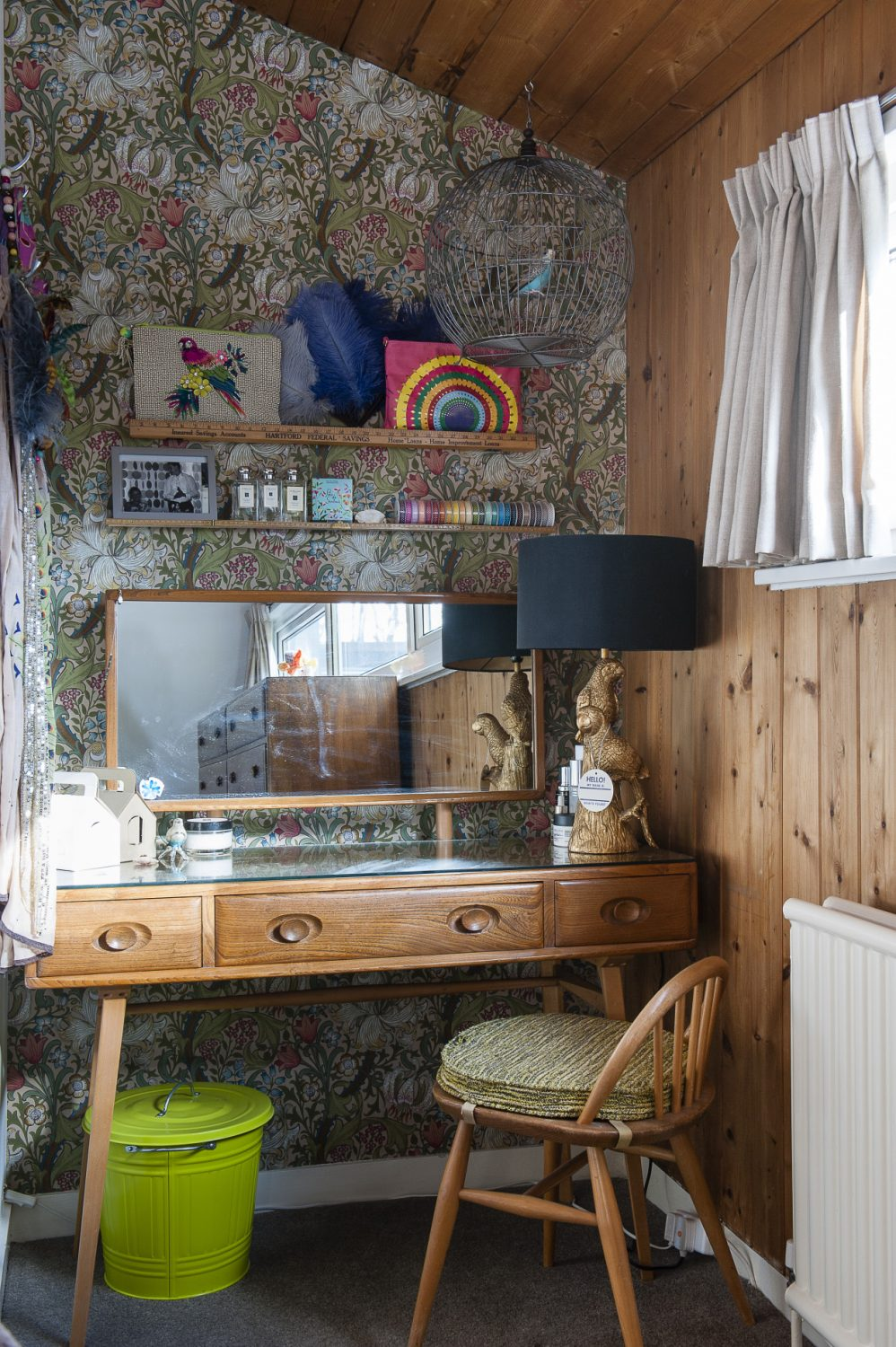 In the corner stands a complementary Ercol dressing table above which have been set delicate narrow shelves made from old wooden metre rulers