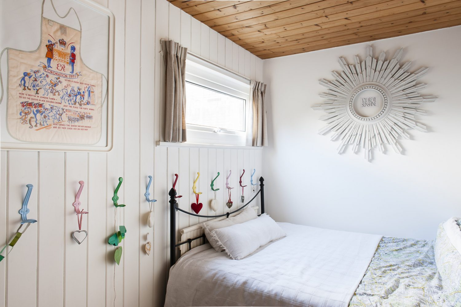 Sam has kept the decor in the smallest room of the house, the spare bedroom, simple by painting the panelled walls a brilliant white which offsets the colourful metal hooks, Ercol furniture and framed commemorative children's aprons perfectly