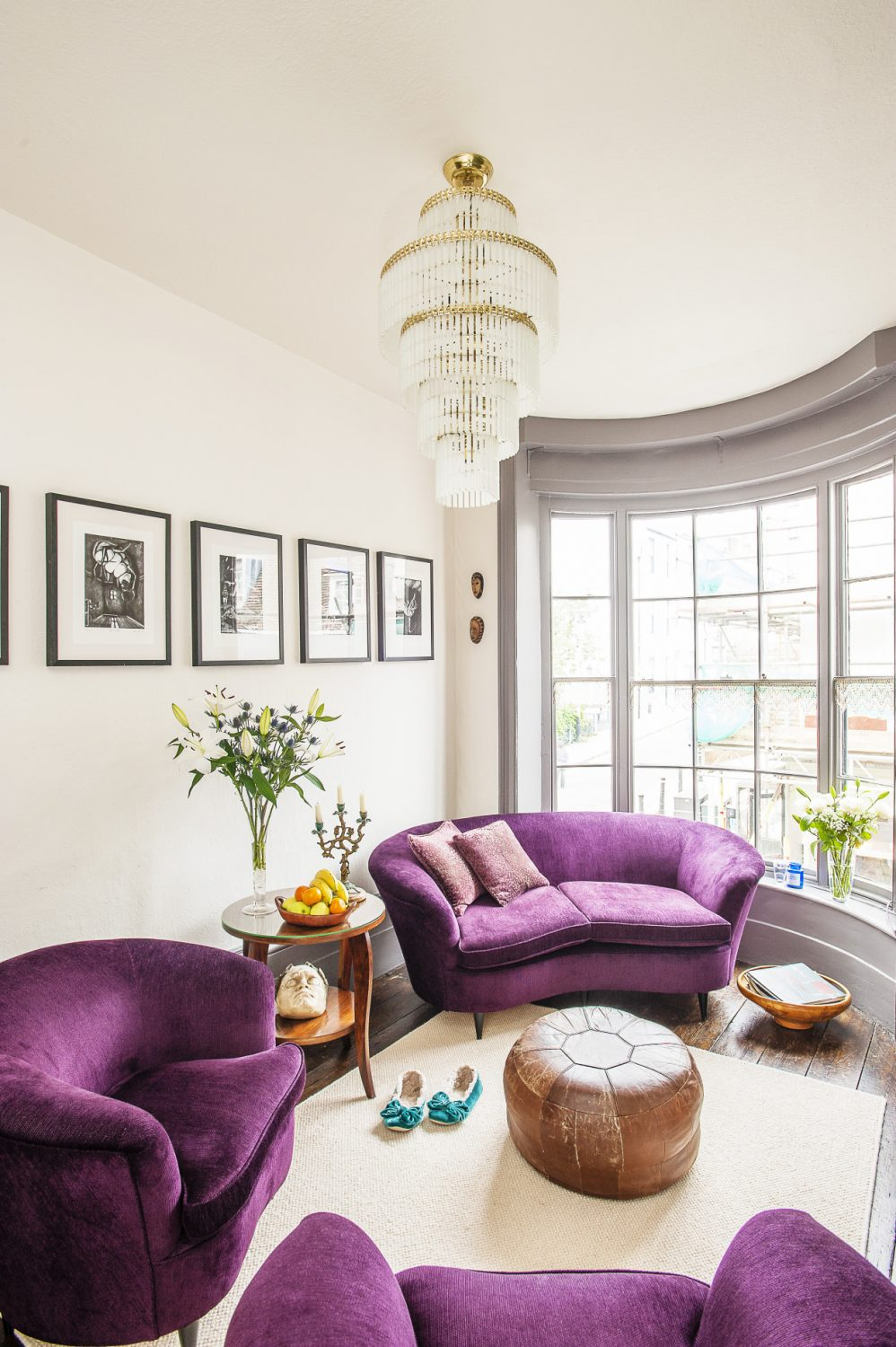 The purple velvet sofa and chairs are 1950s Italian. The plaster head under the coffee table is a 1920s Austrian copy of an antique death mask, from Tallboy Interiors. The prints are by Sassy Luke and the chandelier is 1970s from Chiswick Auctions