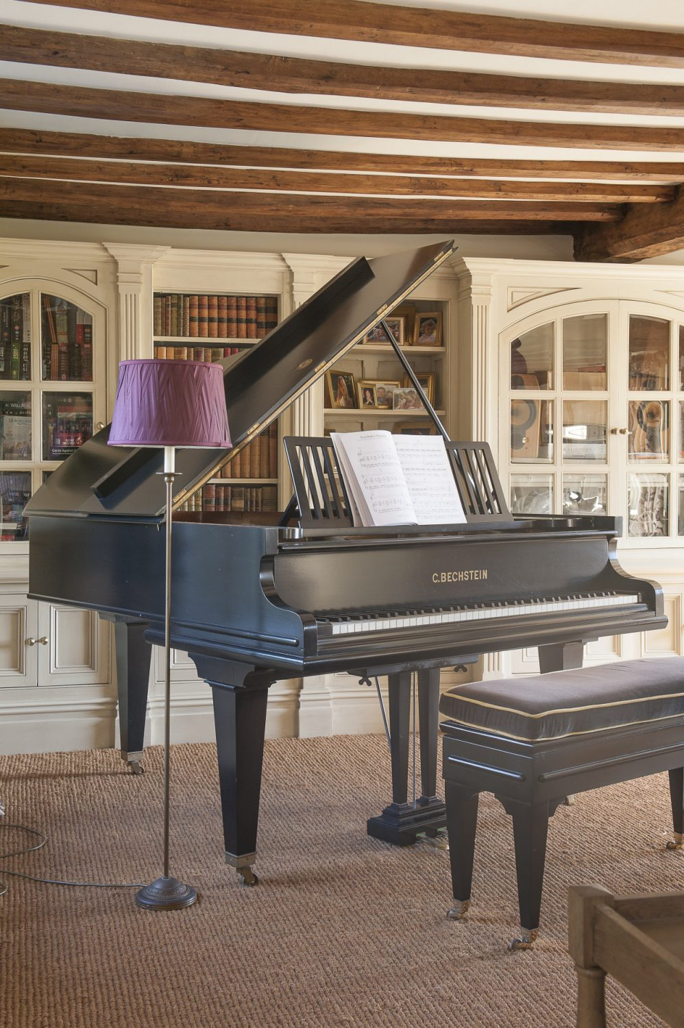 In front of a bookcase that spans one wall of the drawing room stands an impressive grand piano