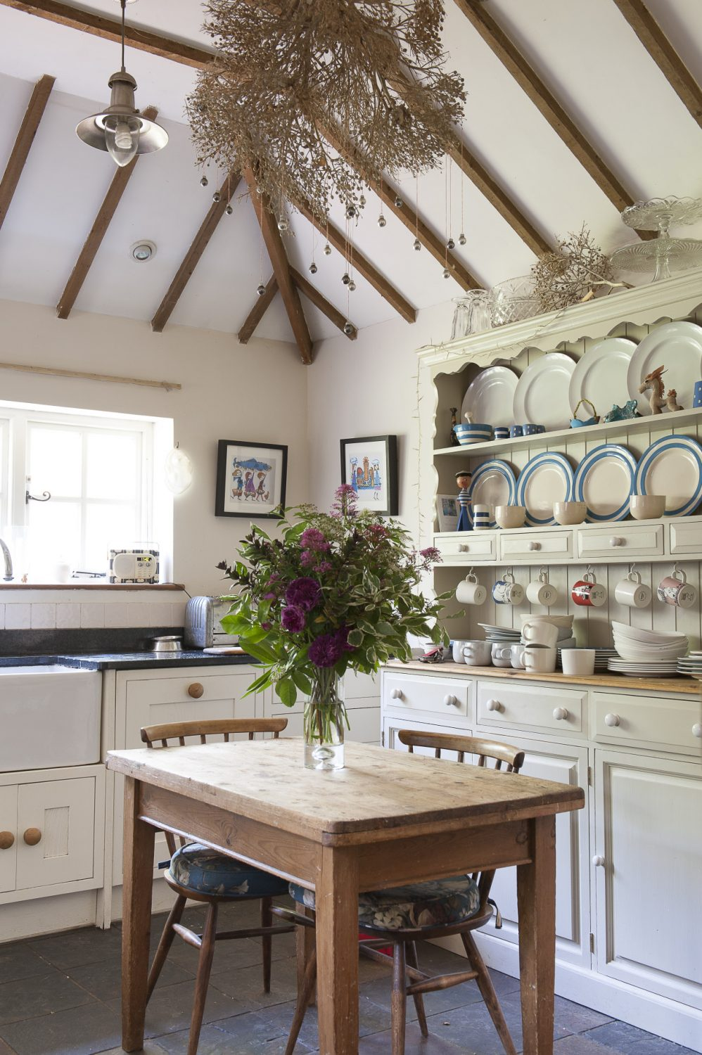 Doors from the dining room lead out into the garden. A dried branch hung with tiny silver baubles forms a quirky chandelier in the high-ceilinged kitchen