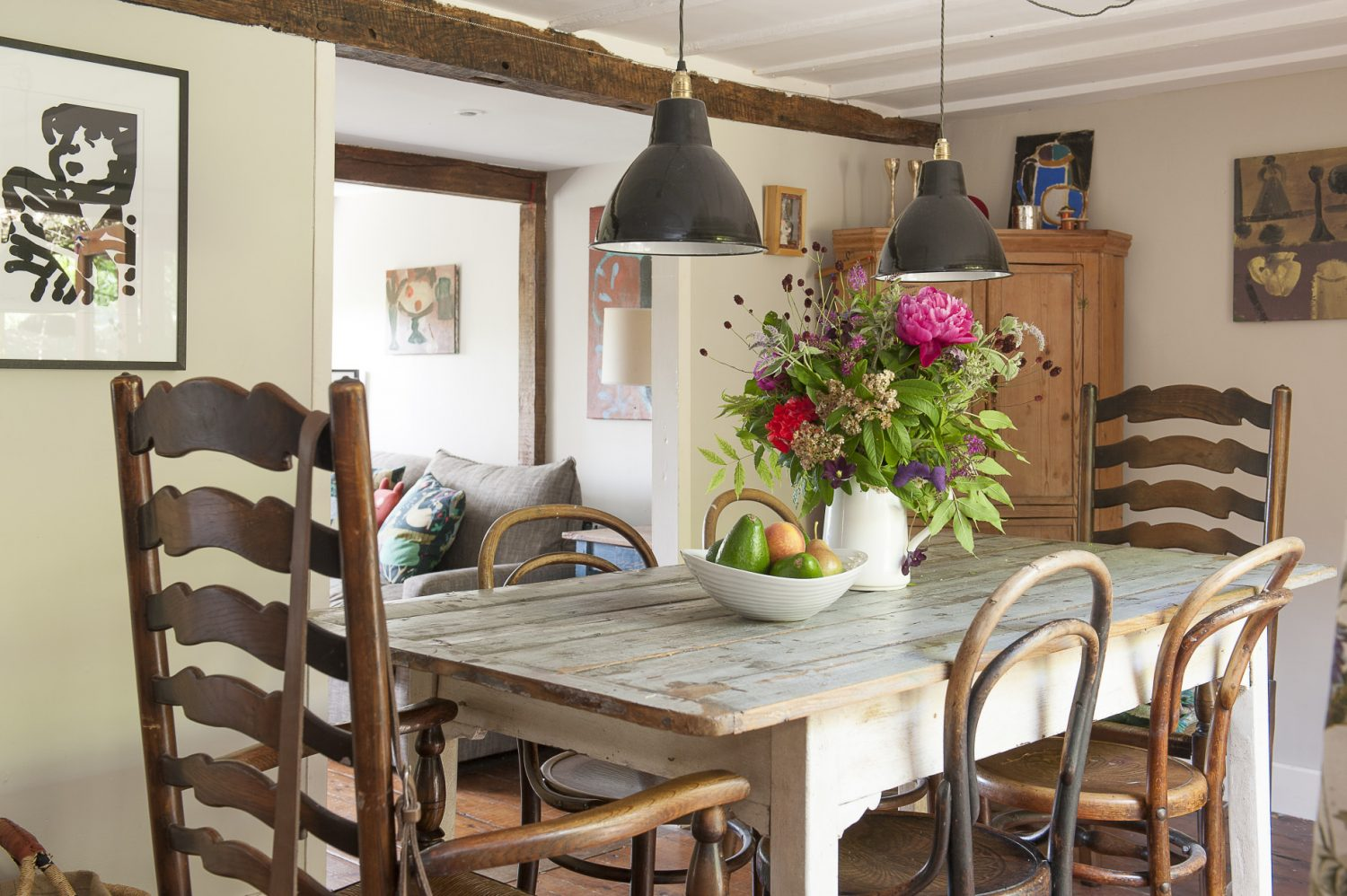 The house's low ceilings add to its 'boat' feel. Mismatched chairs grouped around the dining table and arrangements of cottage garden flowers add country charm