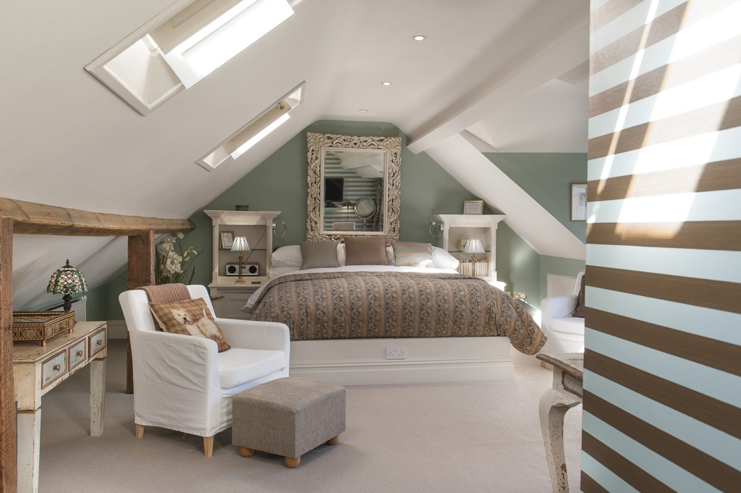 Above Keynes, Sackville is tucked away in the eaves, its vaulted ceiling and clever shutters over the Velux windows providing serious romance. An ornate hand-carved mirror, bought in Battle 30 years ago, hangs above the huge bed