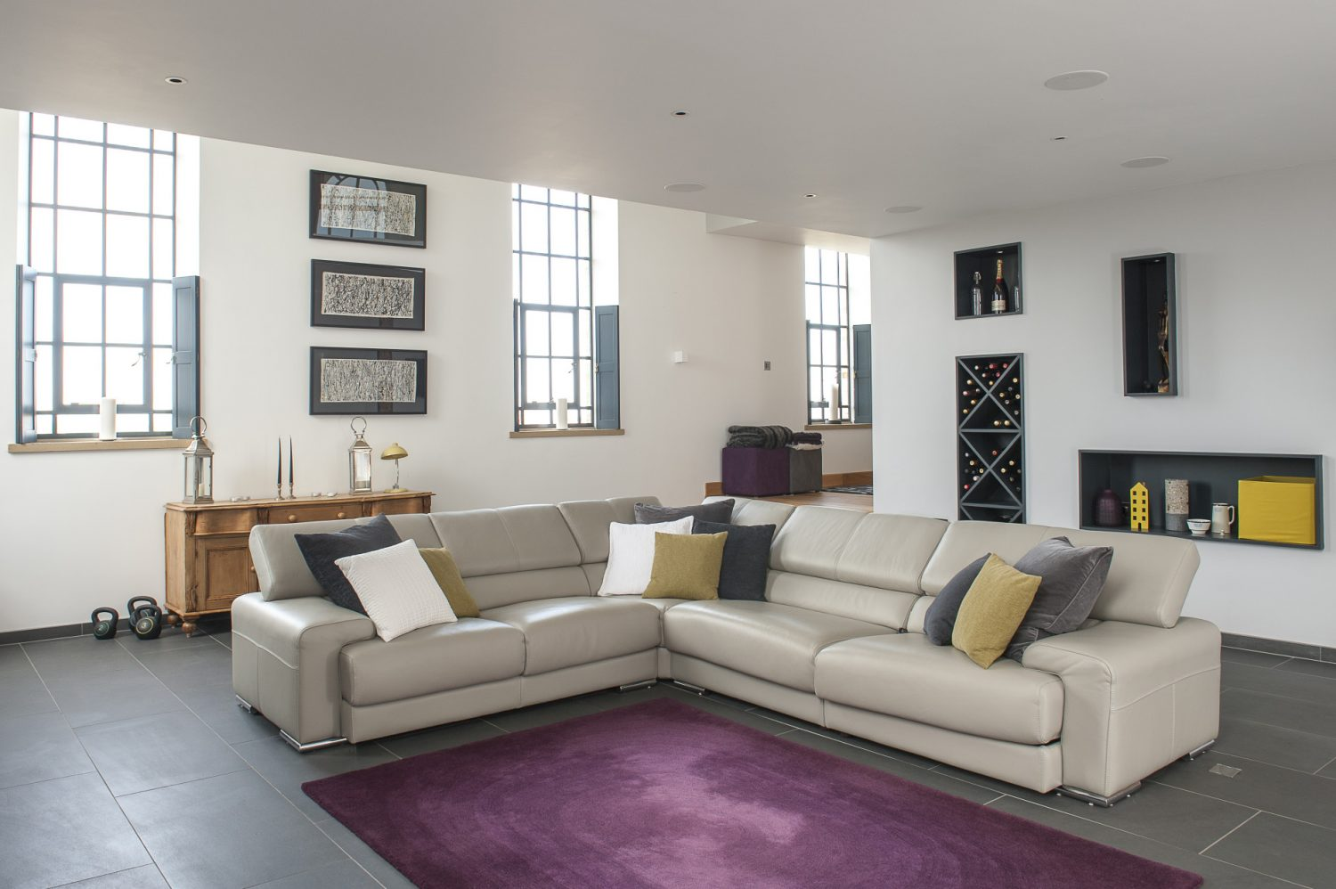 In the sitting room an L-shape of grey Spanish leather Cadira sofas gather round a mauve Habitat rug