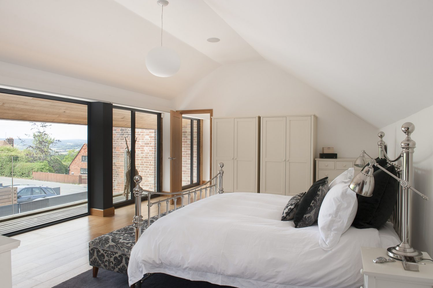 The wall of bi-folding doors is echoed upstairs in the master bedroom directly above the kitchen where they open out onto a decked balcony and more Lloyd Loom surrounded by a plate glass balustrade. The polished nickel bed is from Feather & Black in Tunbridge Wells while above it hangs a wonderful glass Flos Glow Ball light which can be dimmed to look like the moon