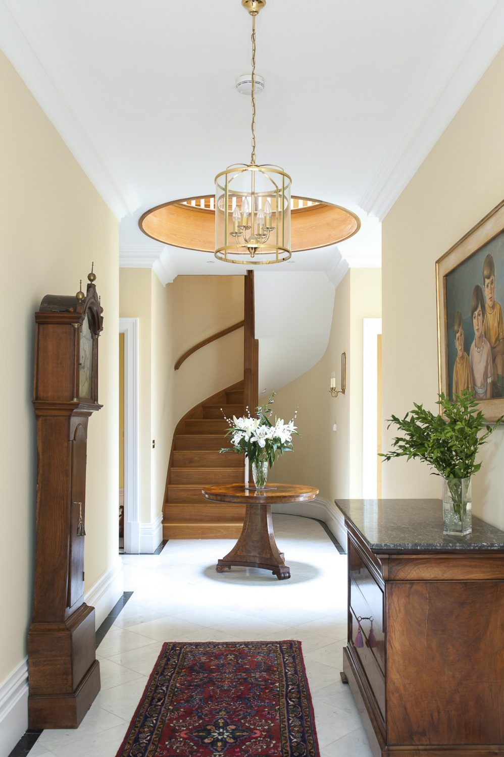 At the heart of this modern rectory-style home is a dramatic entrance hall, flooded with light and filled with furniture that befits the Georgian era