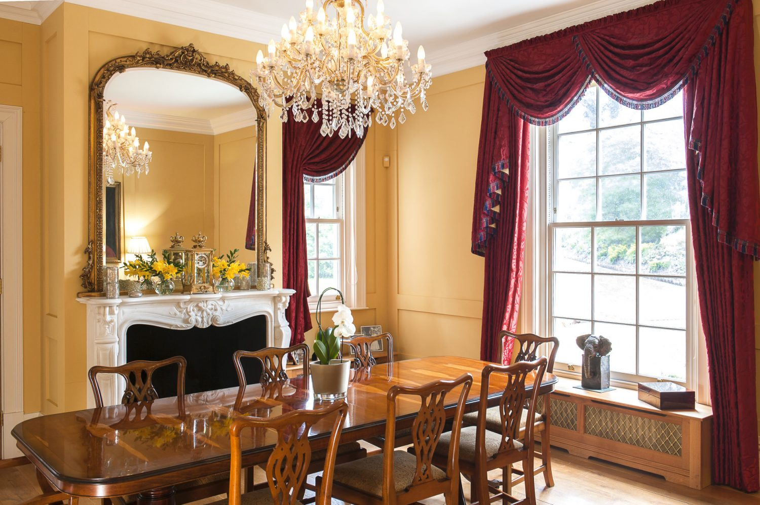 The formal dining room, to the front of the house, is painted in Farrow & Ball's 'Hay' which, paired with blood red damask curtains, makes a wonderfully atmospheric space in which to entertain. The magnificent fireplace is one of many sourced from Chesneys in London